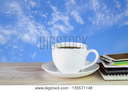 Coffee cupsmart phone and note book on wooden table with blue sky background.Business concept