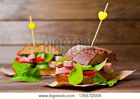 Sandwich with smoked meat and vegetables on a wooden background. Selective focus.