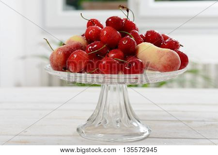 cherries and peaches in a glass cup on wooden table