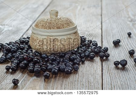 Fresh handful bilberries and old bowl on brown wooden background