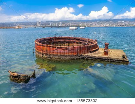 The top of a sunken ship in Pearl Harbour, Hawaii, with Honolulu in the background