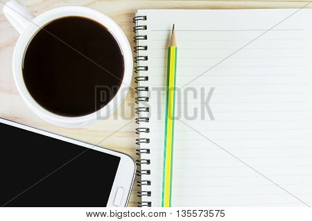 Smart phone coffee and book blank with pencil on wood table background. top view