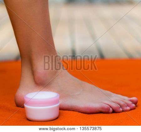 Clean and nice feet on an orange background, a pot of pink cream on the side.