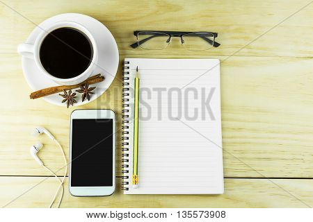 Smart phone coffeeglasses and book blank with pencil on wood table background. top view