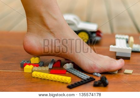 A foot standing up on Color blocks toys of various colors.