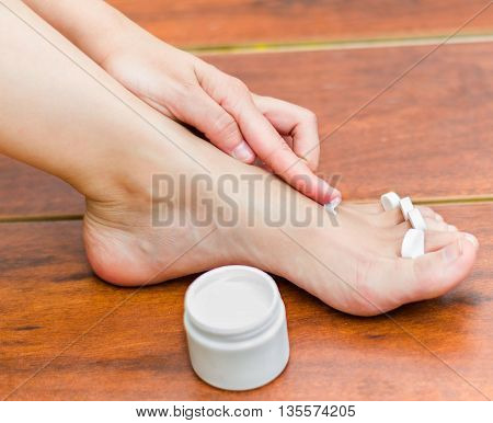 A woman hand applying moisturizer in her feet, best way to hydrate the skin.