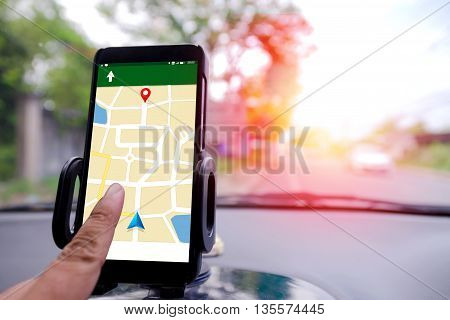 Hand using mobile smart phone GPS navigator selective focus shallow depth of fileld road bacground with sunray effect