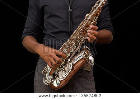 Nice hands touching a silver saxophone, black background.