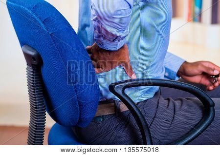 Man apparently working, sitting in a chair and holding his back, pain signal.