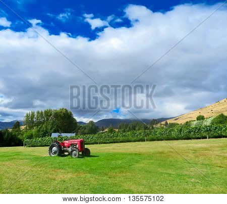 Red tractor in grassy field on a sunny day