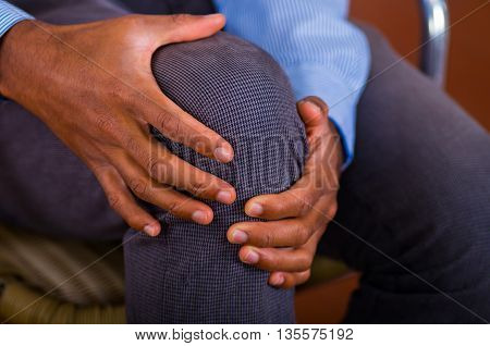 Knee pain on a man, both hands holding it and making some massage.