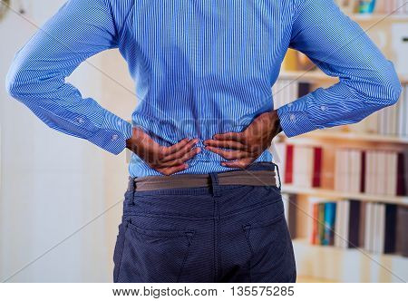 Man touching his back with his two hands, back pain.