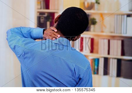 View from the back, man touching his neck with his hands. Pain signal.