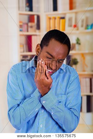 Man with blue shirt, stand up and holding his cheek with both hands, toothache pain.