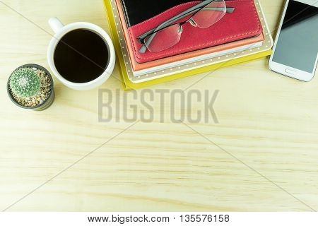 Office desk table with notebooksglasses smart phone and a cactus with cup of coffee.Top view with copy space. Business concept