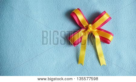 Pink and yellow color ribbons and bow party favor gift on blue fabric background