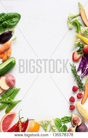 Food background border flat lay of rainbow coloured fresh fruits and vegetables, carrot chilli cucumber purple cabbage spinach rosemary herb, plenty of copy-space