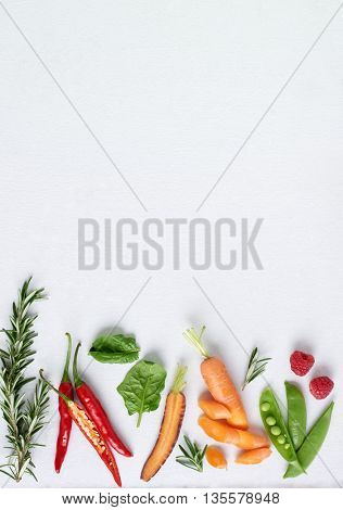 Organic fruit and vegetables herbs on white background, rosemary, chilli, spinach, heirloom carrots, raspberry, plenty of copy space