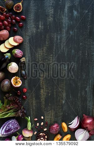 Collection of fresh purple toned vegetables and fruits on distressed background, eggplant, onion, plum, carrot, fig, aubergine, grapes, radishes, loose leaf lettuce, beans passion fruit, cherries