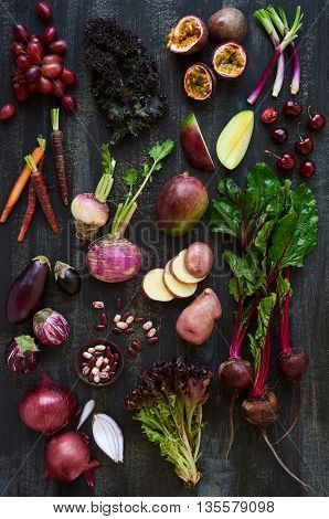 Assortment of fresh purple colored fruit and veg on dark rustic distressed  heirloom carrots, passionfruit, aubergine, grapes, turnip, loose leaf lettuce, kidney beans, spring onions, potato