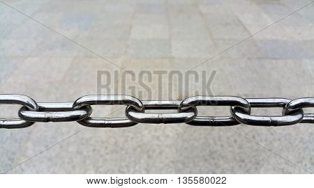 Close up of Metal chain links on grey floor background