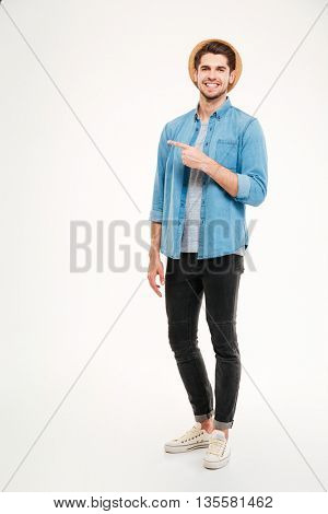Handsome young man pointing away and smiling while standing against white background