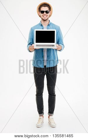 Full length of happy young man in sunglasses and hat holding blank screen laptop