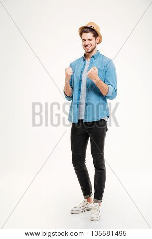 Full length portraitt of a casual handsome man in hat rejoices isolated on the white background