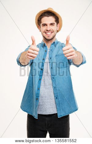 Cheerful young man showing thumbs up isolated on a white background