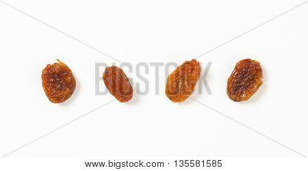four raisins on white background