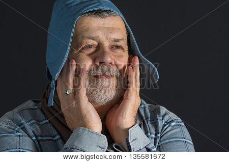 Indoor portrait of senior man in blue shirt and cap being happy