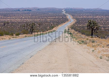 A Deserted Road In The Middle Of The Desert