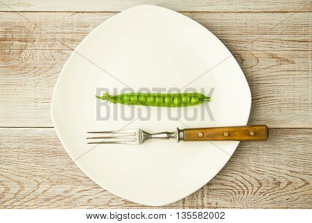Green pea pod and fork on the white plate.