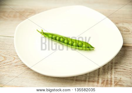 Green pea pod on the white plate.