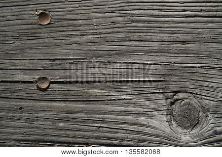 Rustic wooden texture with old rusted nails and a knot