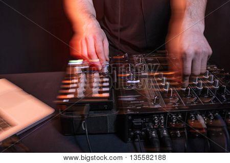 Hands of male dj playing music in nightclub