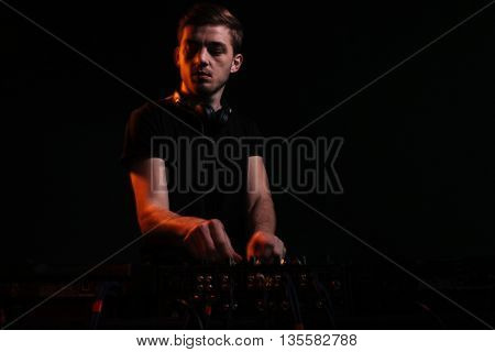 Young DJ playing music at mixer on colorful foggy background