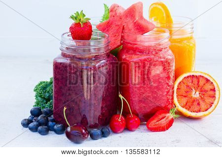 Colorful fresh smoothy drinks in glass jars with igredients