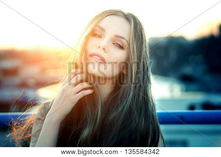 Outdoor portrait of young pretty sexy woman with magic eyes posing at roof at the end of bright sunset. Lovely soft back light.