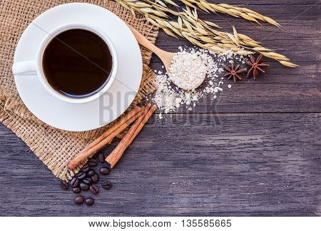 Ears of wheat and cup of coffee on a dark wooden table background