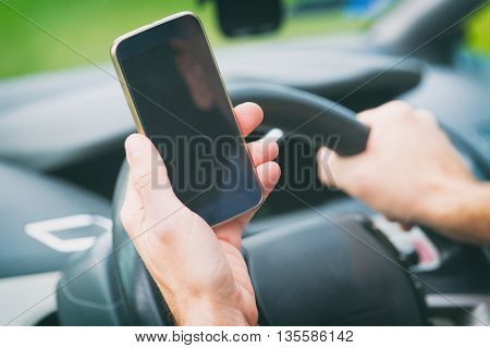 Man using smart phone while driving