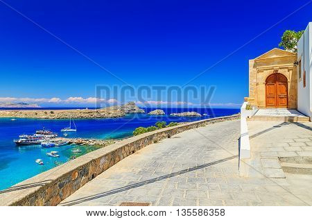 beautiful house in Lindos on the background of bay, yachts and ships of Rhodes Greece