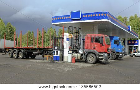 Two empty timber trucks at a gas station