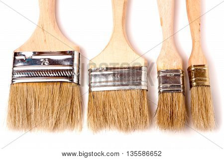 Four different size paint brushes isolated on white background.