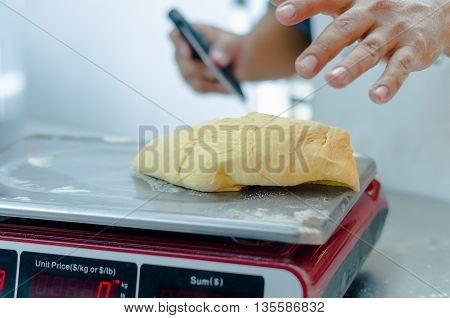 Bakers hands working and weighing bread dough on digital scale .
