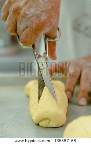 Bakers hands holding scissors above prepared bread dough roll.