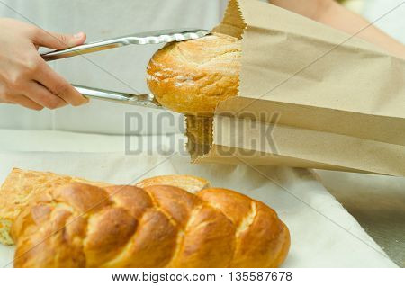 Bakery worker placing loaf of bread inside brown paper bag using large silver tweezers.