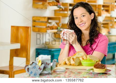 Pretty brunette woman sitting at table inside bakery, holding cup of coffee and smiling happily, bread selection in front.