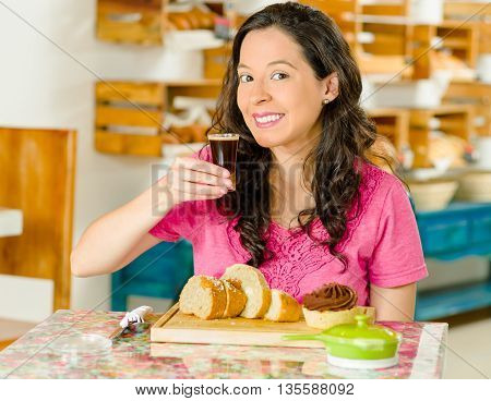 Pretty brunette woman sitting by table inside bakery, holding up hot espresso shot glass and posing for camera.