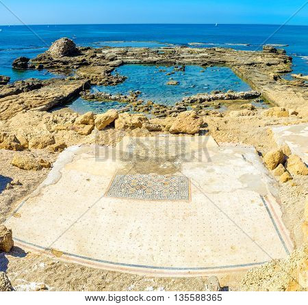 The preserved tiled floor of the ancient building covered with the patterns on the rocky shore in Caesarea Israel.
